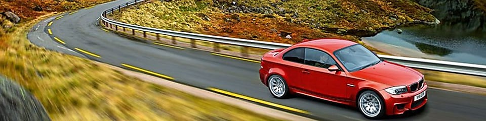 Red sedan driving on the road in Norway