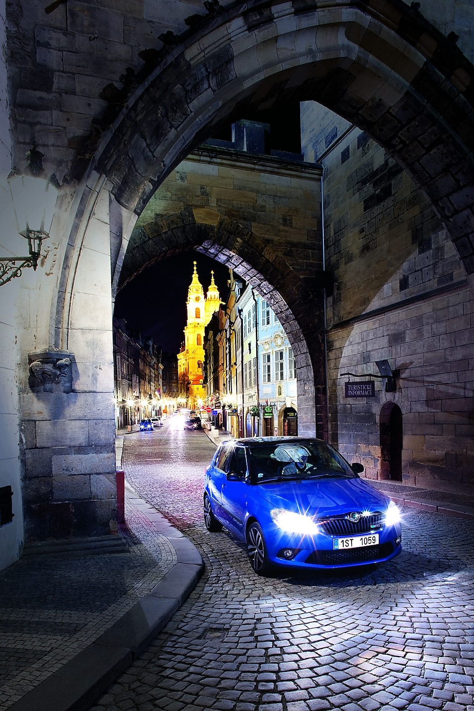 Blue car parked under an arch on a cobbled Prague road at night