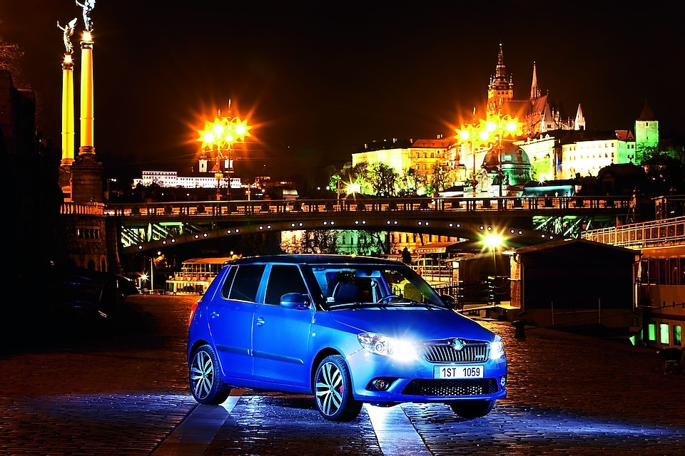 Blue car parked on a Prague road with a bridge and castle in the backdrop, at night