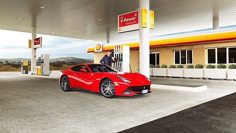 A red Ferrari sitting on a Shell station forecourt with a man leaning on a petrol pump